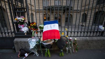 Flowers and a French flag bearing the message 'Paris, Brussels, Solidarity' adorn the entrance of the Belgian embassy in Paris. (AAP)