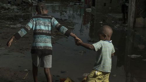 Children walk through the flooded streets of the city of Beira, Sofala Province, Mozambique, after Cyclone Idai made land fall.