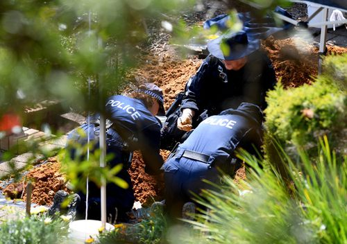 NSW Police and Forensic Services personnel sift through dirt as they search the former home of missing woman Lynette Dawson, at Bayview on Sydney's northern beaches.