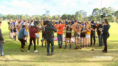 Two opposing football teams stood arm-in-arm observing a minute's silence for the 22-year-old today. Picture: 9NEWS