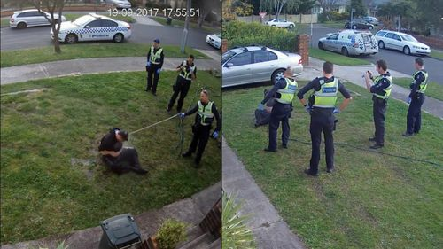 An officer then sprays the man with a watering hose while another draws out his mobile phone to film. (Fairfax Media)