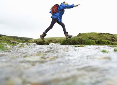 Female hiker jumping over stream