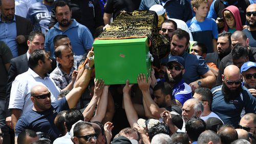 Mourners carry Jihad's coffin at a ceremony for the schoolboy. (AAP)