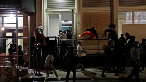 People rush into a Gucci store after it was broken into, in New York, as protests rage over the death of George Floyd.