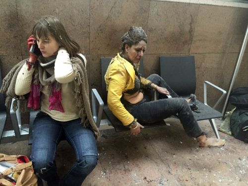Two injured women sit dazed, confused and covered in dust in Brussels Airport in Belgium, on March 22, 2016. Twin bombings at Brussels airport and a metro station killed 32 people from around the world. Islamic State claimed responsibility for the attack.