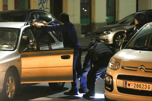 Police officers check a person after gunshots were heard in Vienna
