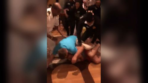 People can be seen fighting in mobile footage before security guards step in and pin passengers to the ground, kicking them in an attempt to separate them (Supplied).