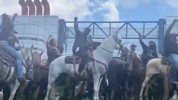 Horsemen and women raise their arms in solidarity for George Floyd.