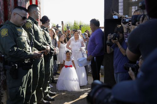 """Evelia Reyes, along with her daughter, watches at the """"Door of Hope"""", part of the for the border fence, for her fiance, Brian Houston to walk up for their wedding (Howard Lipin//The San Diego Union-Tribune via AP)"""