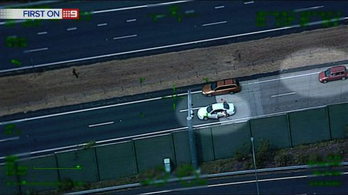 The men sprint into traffic chased by police. (9NEWS)