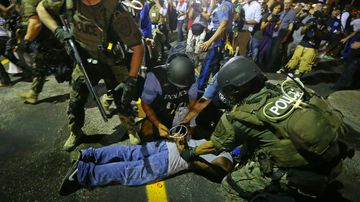 Police arrest a man after breaking up a protest in Ferguson. (AP)