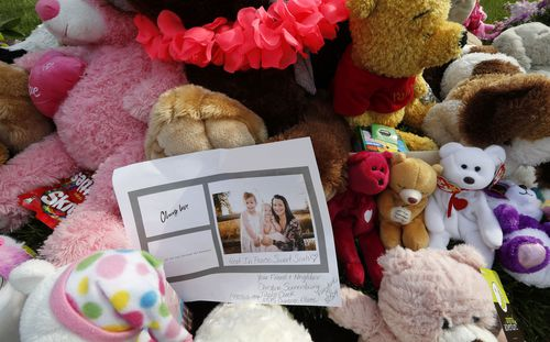 A photograph sits amid the tributes as they grow outside the home.