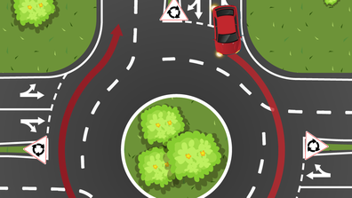 A red car tries to drive around a roundabout in the left lane