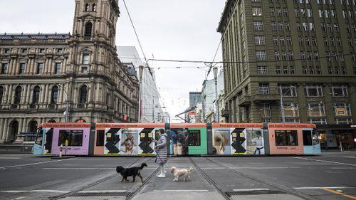A person crosses Bourke Street in Melbourne, Australia. Victoria is under strict lockdown.