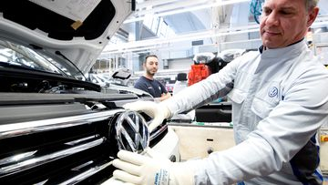 An employee shows a VW logo shortly before installation in a Volkswagen Touran in final assembly at the VW plant.