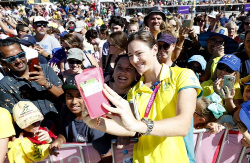 Swimmer Cate Campbell poses for a selfie with waiting fans on the Gold Coast this morning. (AAP)