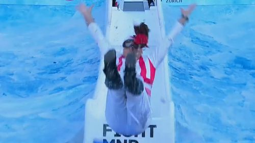 "Sydney Swans coach John ""Horse"" Longmire looked ""giddy"" as he slid into the icy water below. (9NEWS)"