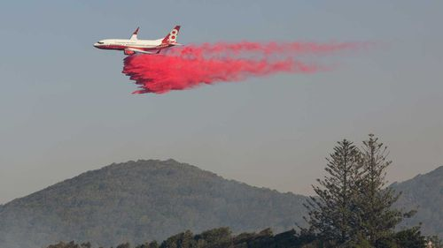 A water bombing plane drops fire retardant on a bushfire at Forster, NSW mid-north coast.