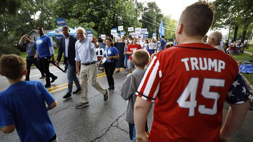 Bernie Sanders waves to a Donald Trump supporter during a parade in Iowa.