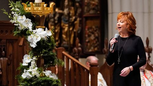 US singer Reba McEntire sings 'The Lord's Prayer' during a funeral service.