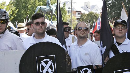 James Alex Fields Jr., second from left, holds a black shield in Charlottesville, Va., where a white supremacist rally took place. Fields was later charged with second-degree murder and other counts after authorities say he plowed a car into a crowd of people protesting the white nationalist rally. (AP)
