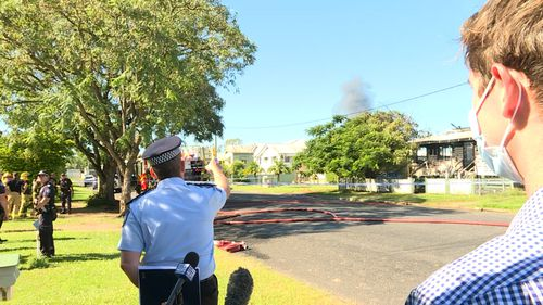 A fire has erupted behind a police officer while he was talking to a news crew about an unrelated deadly fire