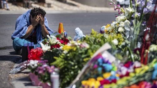 An El Paso man weeps beside a makeshift memorial for victims of the Wal-Mart massacre.