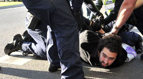 A protester who lunged at Julie Bishop is wrestled to the ground by police. (AAP)