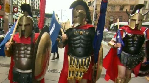 People dressed as Spartans and carrying Eureka flags in Martin Place. (9NEWS)