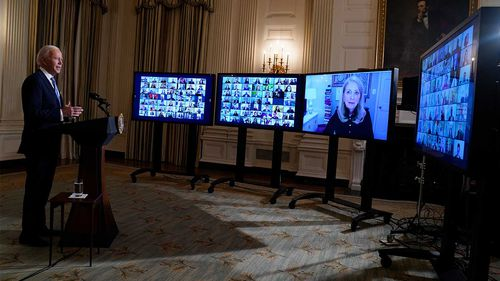 President Joe Biden listens during a virtual swearing in ceremony of political appointees from the State Dining Room of the White House.