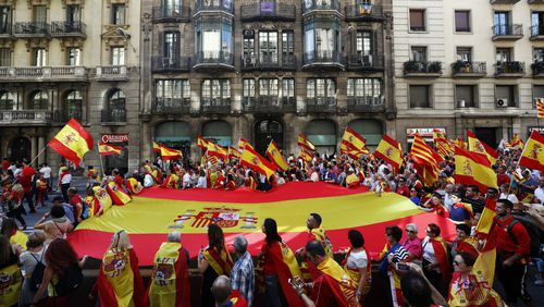 Protestors carry a giant Spanish flag during a rally in favour of the unity of Spain in Barcelona. (AAP)