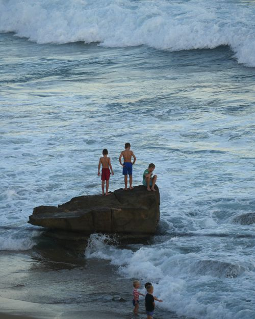 Children play near the shore as residents of Newcastle, New South Wales, look for alternative ways to beat the heat as beaches are closed for a seventh consecutive day in January 16, 2015 due to shark sightings at popular beaches. (AAP)