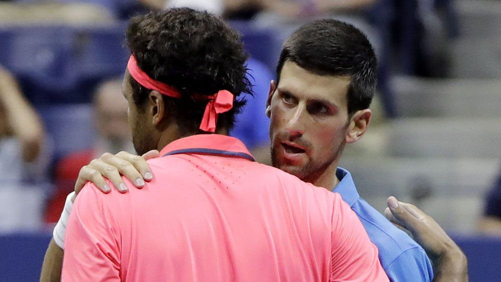 Novak Djokovic (r) consoles Jo-Wilfried Tsonga after the Frenchman was forced to retire at the US Open. (AAP)