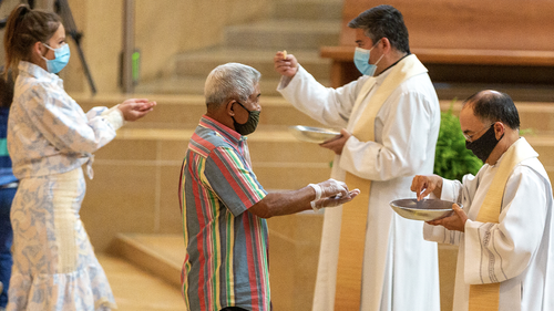 The faithful wear masks and some wear gloves as they receive Communion at the first English Mass with faithful present at the Cathedral of Our Lady of the Angels in downtown Los Angeles, Sunday, June 7, 2020.