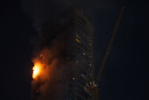A fire burns on the side of a high-rise building in Sharjah, United Arab Emirates