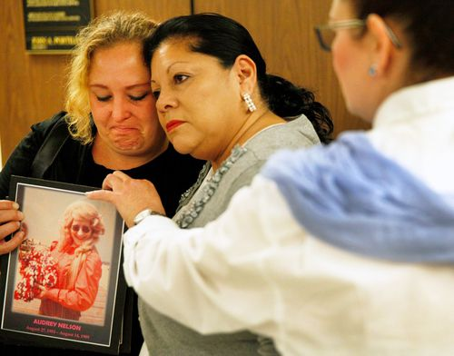 Pearl Nelson, 38, is hugged by Mary Louise Frias. Ms Nelson is holding a photo of her mother, Audrey Nelson – a victim of convicted serial killer Samuel Little. Ms Fria's godmother, Guadalupe Apodaca Zambrano, was also a victim.