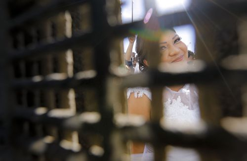 """Evelia Reyes looks into the United States at Friendship Park, part of Border Field State Park, through the border fence from the Mexico side, before getting married to Brian Houston at the """"Door of Hope,"""" part of the border fence between the U.S. and Mexico. (Howard Lipin//The San Diego Union-Tribune via AP)"""