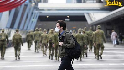 A man wearing a face mask walks past as the Australian Defence Force walk through the city.