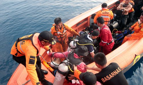 Indonesian navy divers search for the black box flight recorder today.