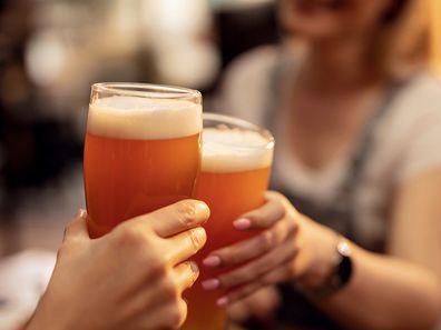 Two people toasting beer in a bar