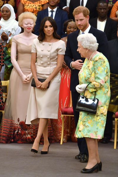 Duchess of Sussex in Prada at the Young Leaders Awards at Buckingham Palace with husband Prince Harry and the Queen, July 2018