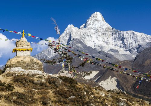 The mountain Ama Dablam (6856m) is seen from behind a Buddhist stupa and prayer flags.