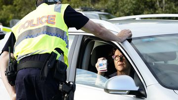 A motorist shows identifcation at a checkpoint on the Gold Coast Highway at Coolangatta on the Queensland/NSW  border , Thursday, March 26, 2020.