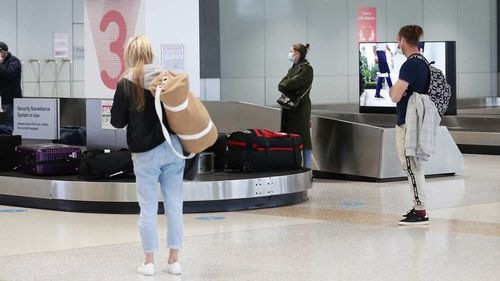 Passengers wait for their luggage.
