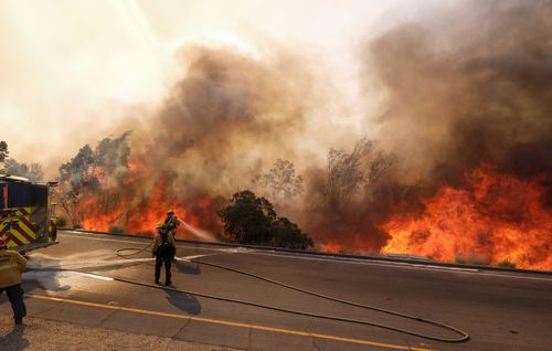 A firefighter battles a fire along the Ronald Reagan Freeway in Simi Valley.
