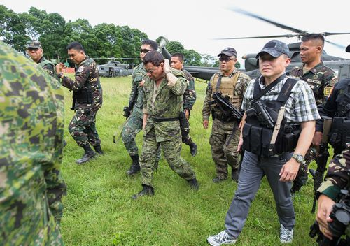 Philippine President Rodrigo Duterte (C), seen carrying a sidearm on his waist, walking to his helicopter after visiting a military camp in Marawi on the southern island of Mindanao. (AFP)