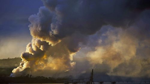 The Eden timber mill wood chip pile burns on Ben Boyd Point, seen across Two Fold Bay from Eden, NSW on Thursday, January 9, 2020.