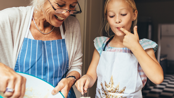 Grandmother with young girl cooking