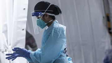 A health worker prepares to carry out COVID-19 testings out at a drive-through clinic (file photo).