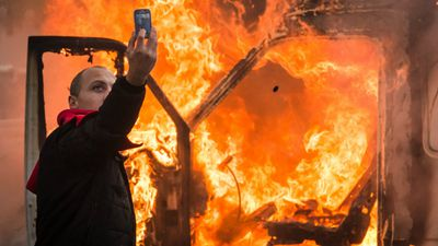 A protester takes a selfie next to a burning car. (AAP)